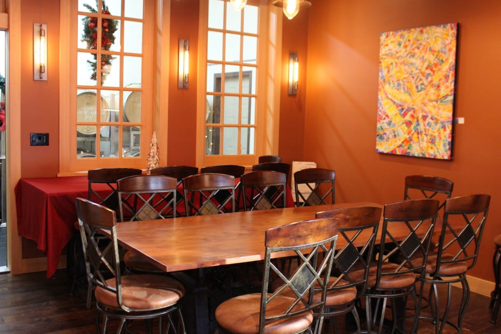 The tasting room is furnished with repurposed printing press tables and Italian sewing machine stools
