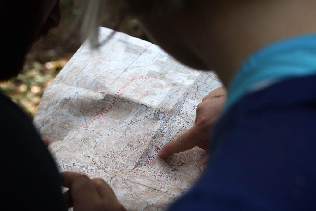 image of two people pointing at a spot on a paper map
