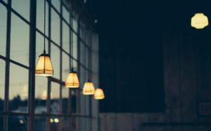 image of lights in a building next to a bank of windows.