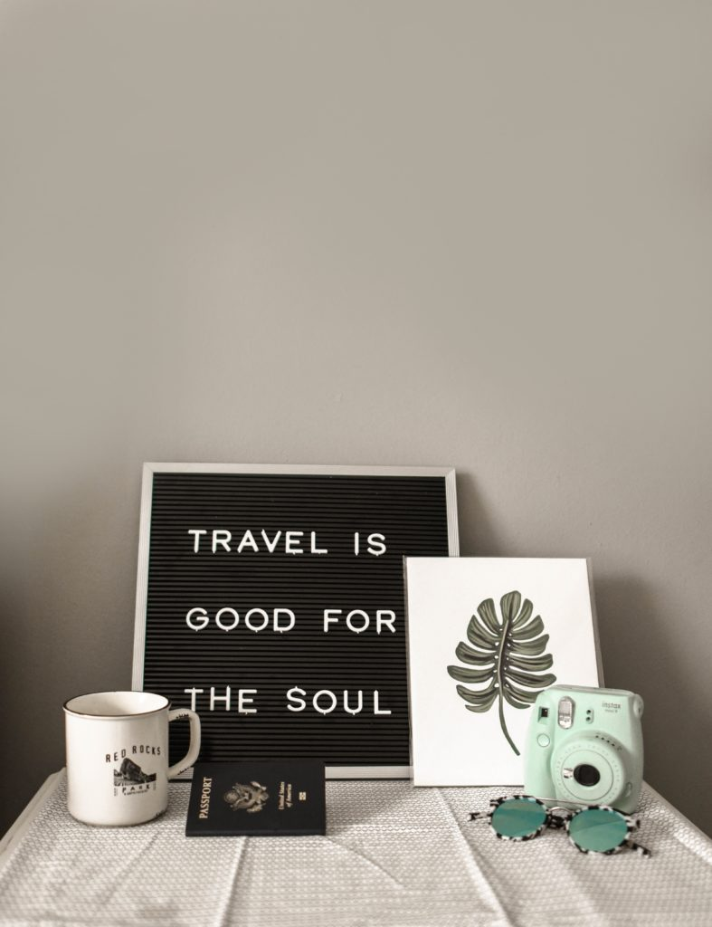 an image of a table with a board that says travel is good for the soul, surrounded by a mug and minimalist artwork